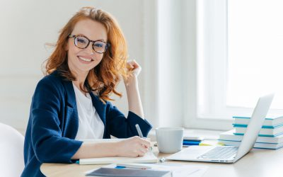 Sideways shot of prosperous businesswoman with foxy hair, smiles positively, records information in notepad, drinks coffee, searches information on laptop computer, develops strartup project